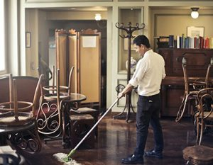 man cleans floors in a restaurant after hours