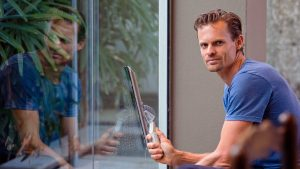 employee poses for picture as he cleans glass if an office building