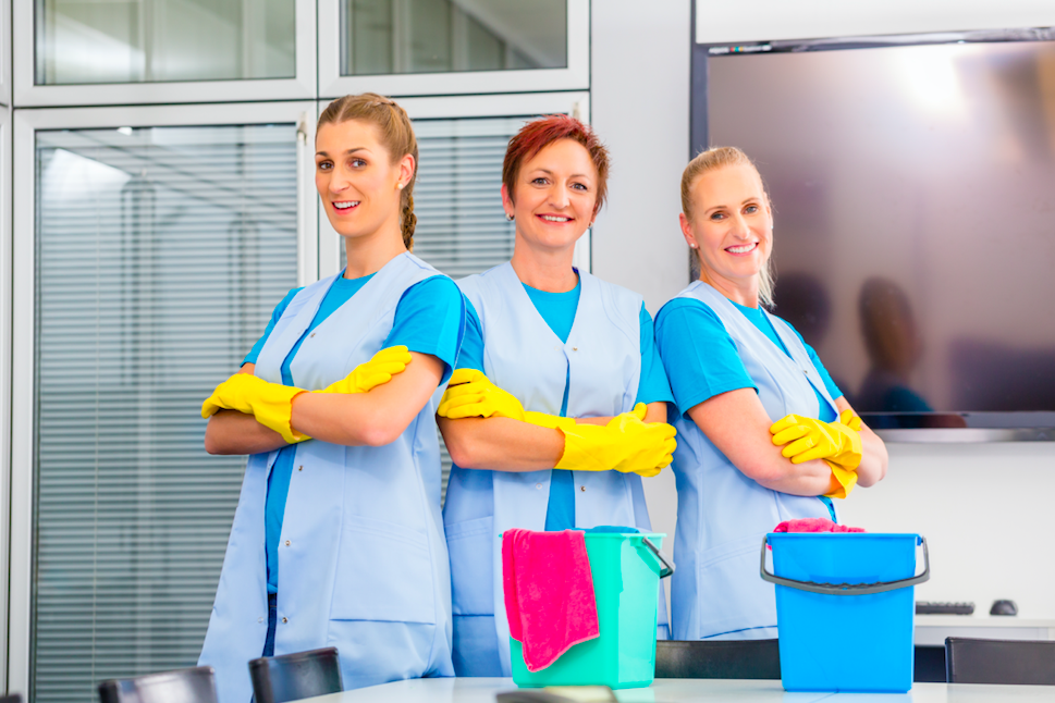 cleaning ladies posing for picture with cleaning supplies on a table
