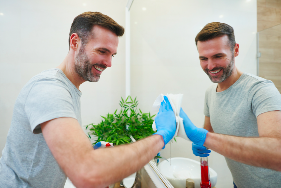 man happily cleans mirror in office bathroom
