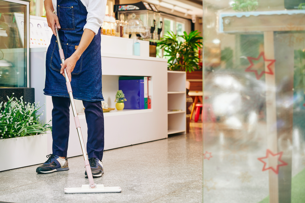 janitor mops floor of business
