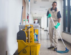janitor mops hallway in office building